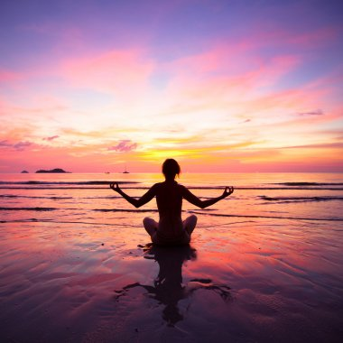 A woman practicing yoga sitting on the beach during sunset
