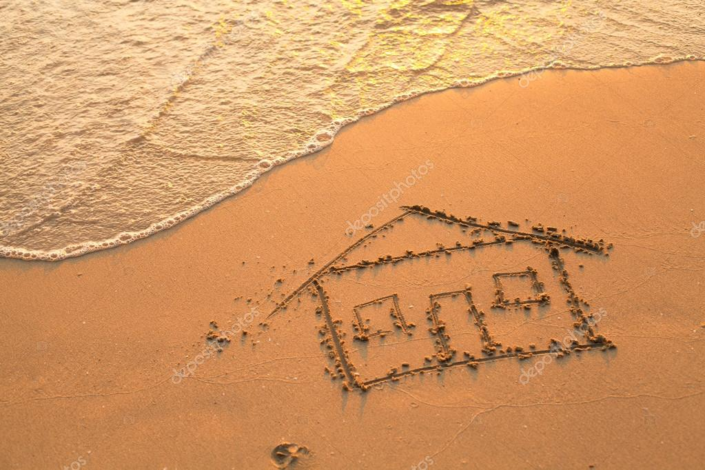 Conceptual photo: a house painted on beach sand