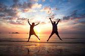 Koncept dlouho očekávaný dovolenou: mladý pár ve skoku na pláži u moře při západu slunce.