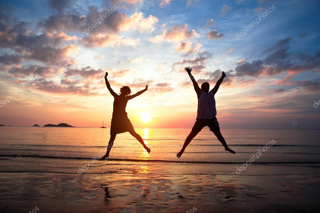 Concept of long-awaited vacation: Young couple in a jump on the sea beach at sunset.