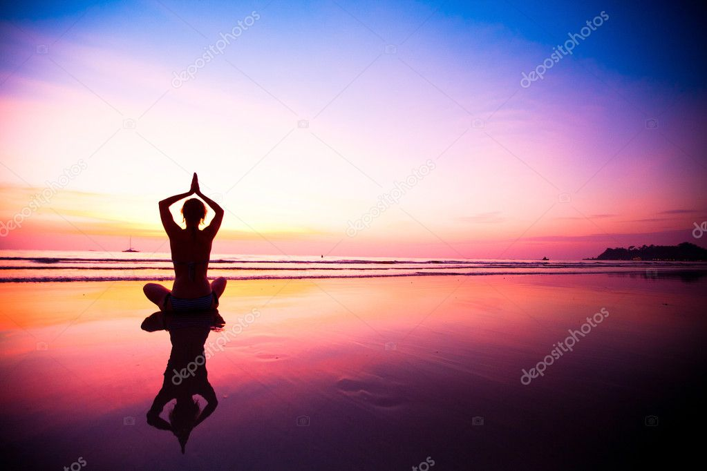 Silhouette of a woman meditating on the beach at sunset