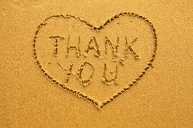 Texture of sand: the inscription inside the heart of Thank You.