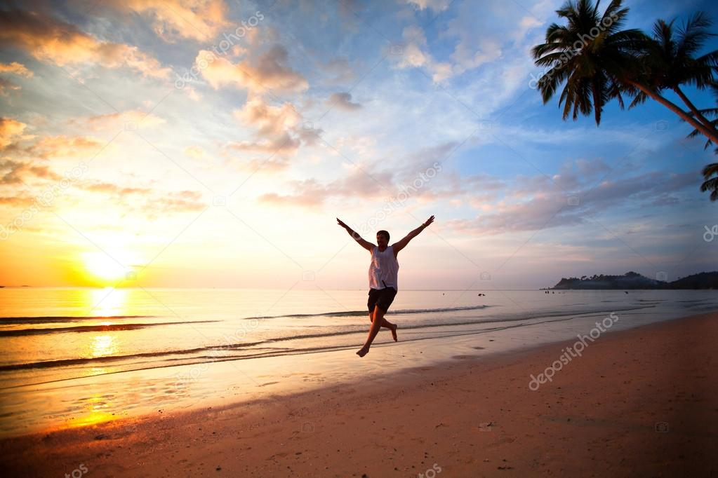 Young fun man running on sea beach at sunset