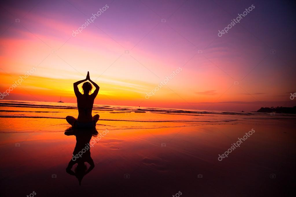 Silhouette of woman practicing yoga on the beach during a beautiful sunset.
