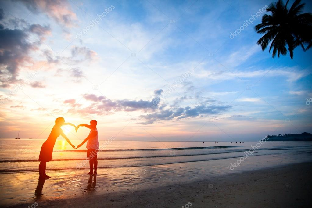 Young Couple Holding Hands Heart Shaped On The Sea Beach At Sunset Stock