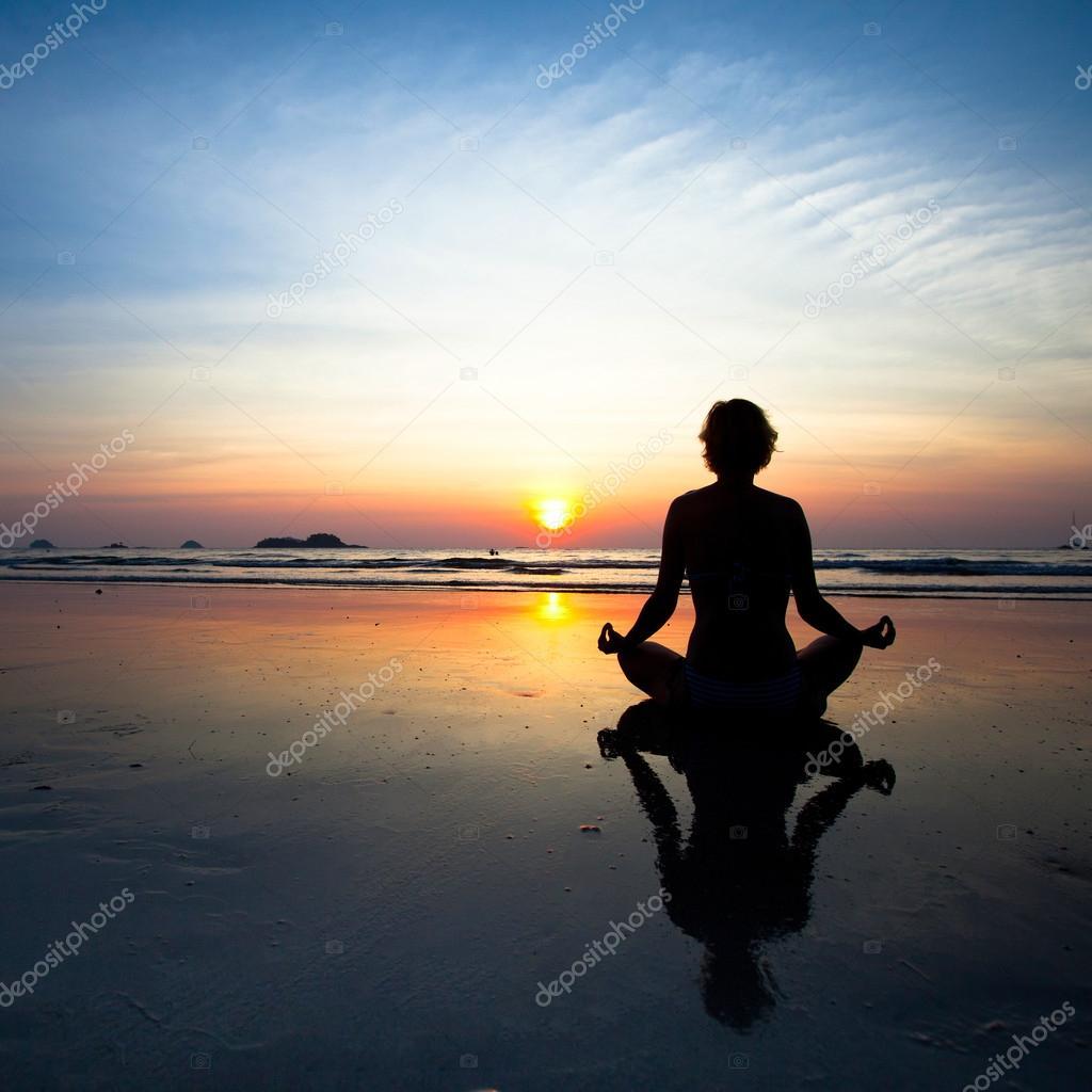 Silhouette yoga woman sitting on sea coast at sunset.