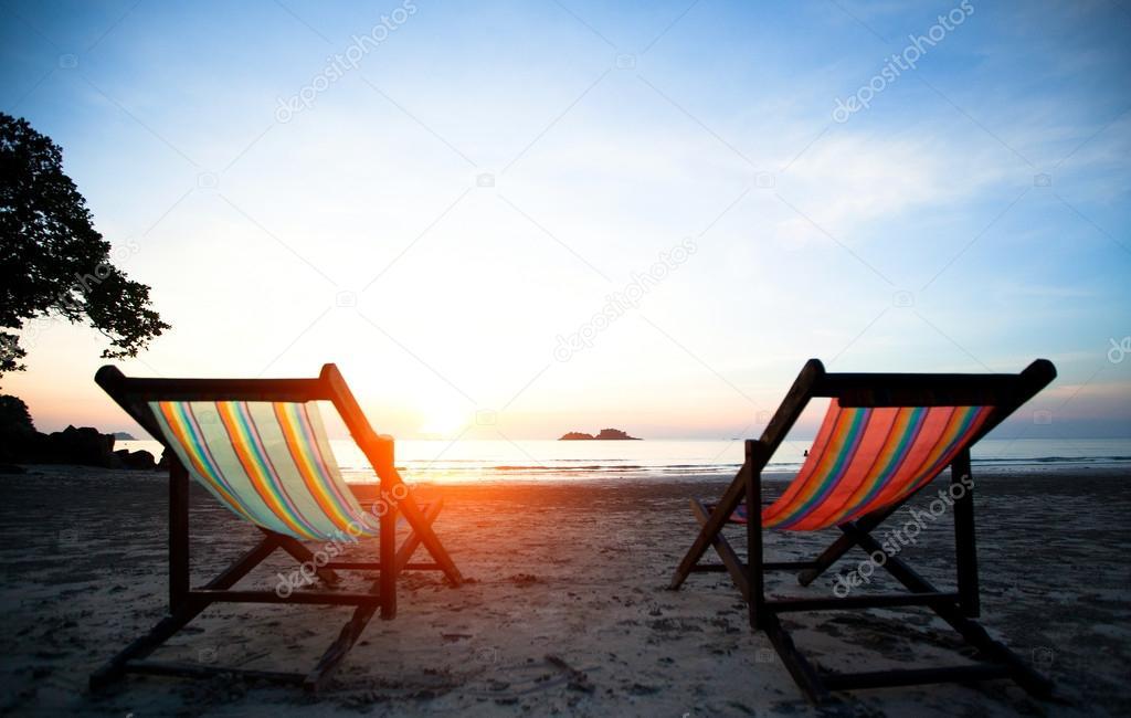 Couple of beach chairs on the evening sea coast