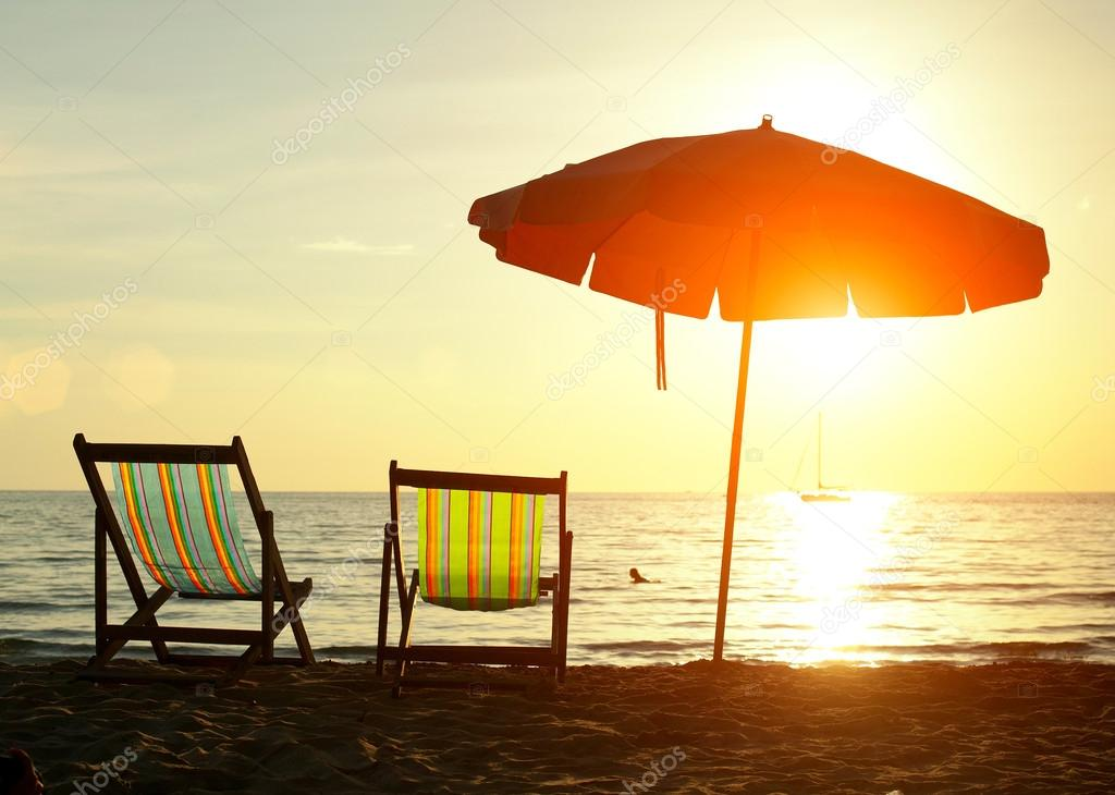 Pair of beach loungers on the deserted coast sea at sunrise.
