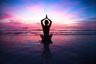 Sunset yoga woman on sea coast