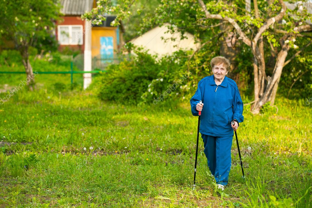 Active old woman nordic walking outdoors (85 years)