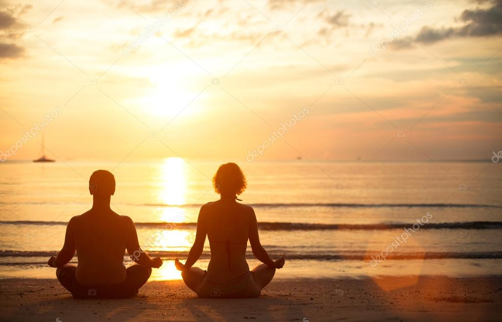 A young couple sitting on the beach of the sea in the lotus position