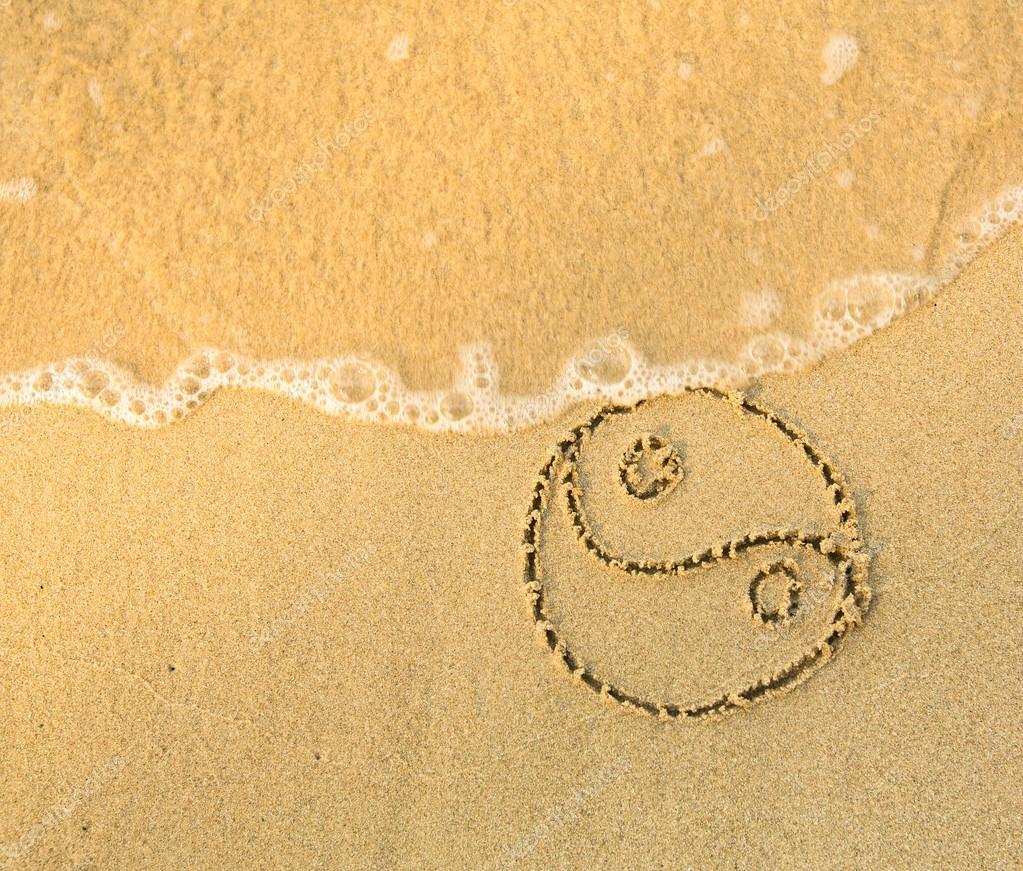 Yin yang symbol - written on sand