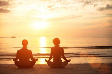 Couple sitting on the beach of the sea in the lotus position