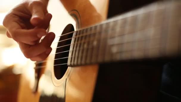 Detailní záběr: prsty se dotýkají strun na kytaře