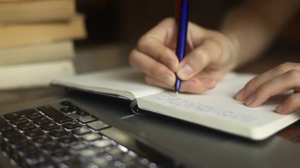 Close-up of a young woman writes a pen in a notebook, laptop and books in the background