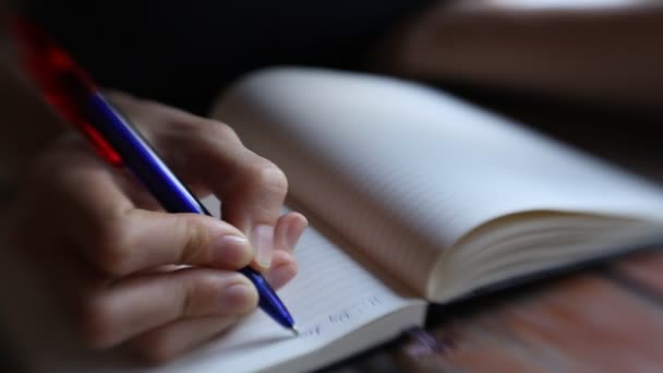 Close-up of hand pen writes in a notebook (blurred)