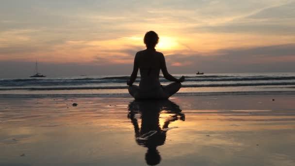 žena mladých jógu, meditace v lotus pose na pláži při západu slunce