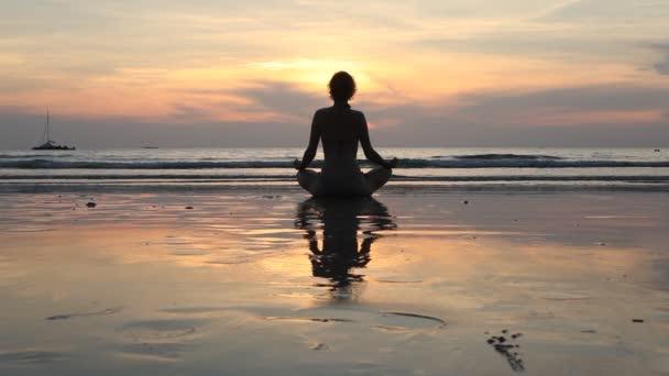 Fiatal jóga nő meditál lótusz póz a tengerparton naplementekor