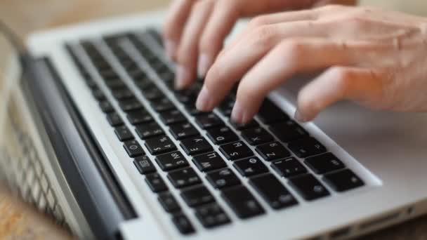 Közeli kép: egy fiatal nő, egy laptop billentyűzet gépelés