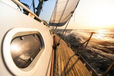 Yacht sailing towards the sunset.