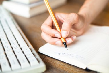 Hands writes a pen in a notebook, computer keyboard in background.