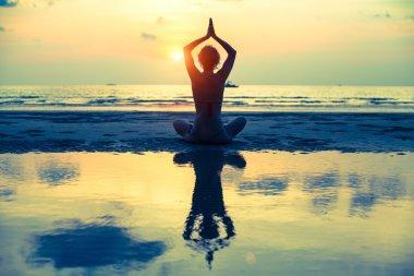 Yoga woman sitting in lotus pose on the beach