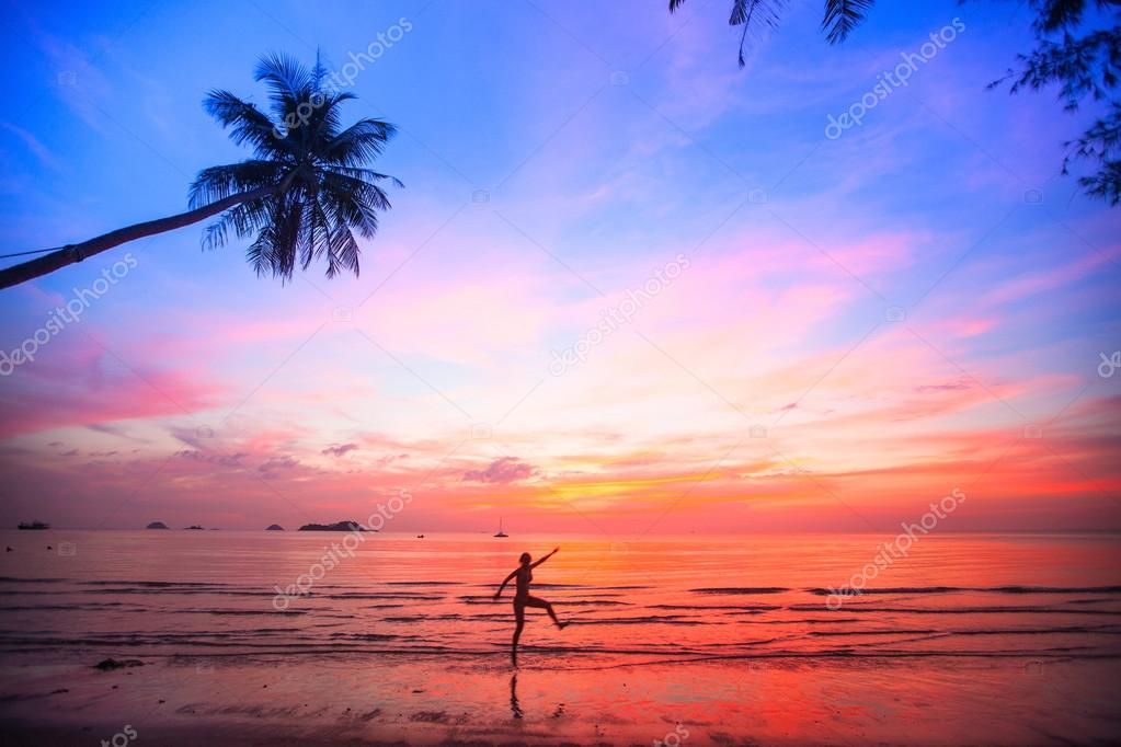 Beautiful sunset with silhouettes of girls on a beach
