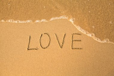 Love - text written by hand in sand on a beach, with a blue wave