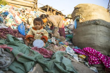 Unidentified child is sitting while her parents are working on dump