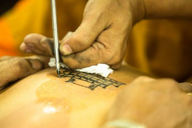 Unidentified monk makes traditional Yantra tattooing