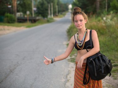 Girl  hitchhiking on countryside road.