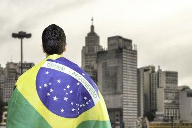 Brazilian holding a brazilian flag looks to Sao Paulo Skyline, Brazil