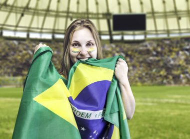 Brazilian fan celebrates on the stadium with her face painted and the flag of Brazil