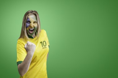 Brazilian woman celebrates on green background with her face painted