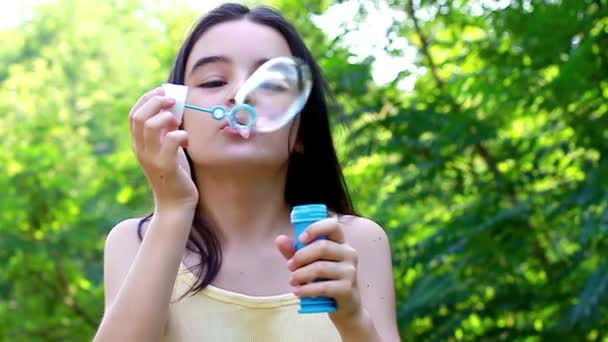 Little cute girl blowing soap bubbles outdoors
