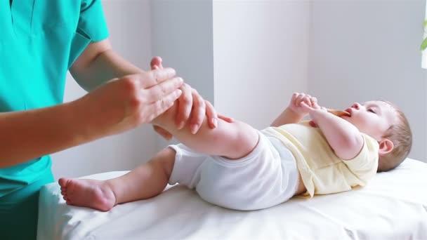 fyzioterapeut masíruje nožkou baby boy