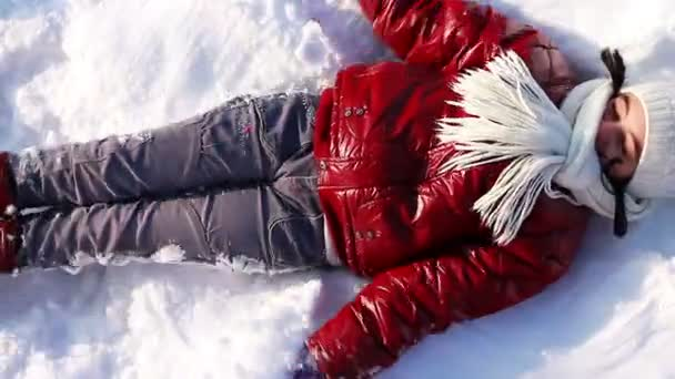 Girl makes a snow angel