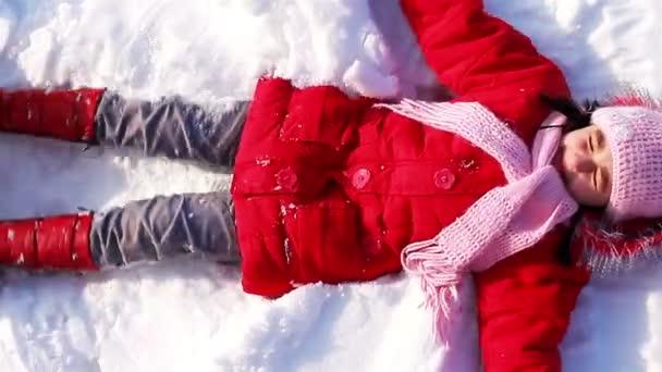 malá holka dělá sníh anděl