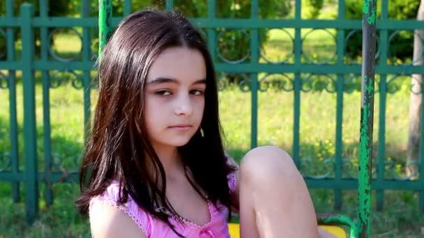 smutná dívka na houpačce