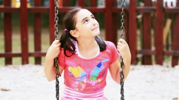 holčička na houpačce se usmívá na kameru