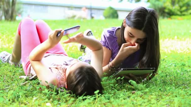 Girls playing on digital tablet and smartphone