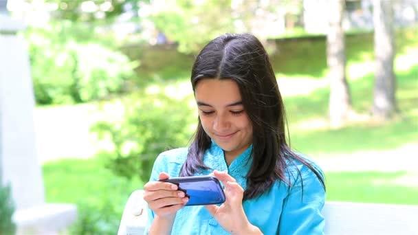 dospívající dívka hrající na smartphonu
