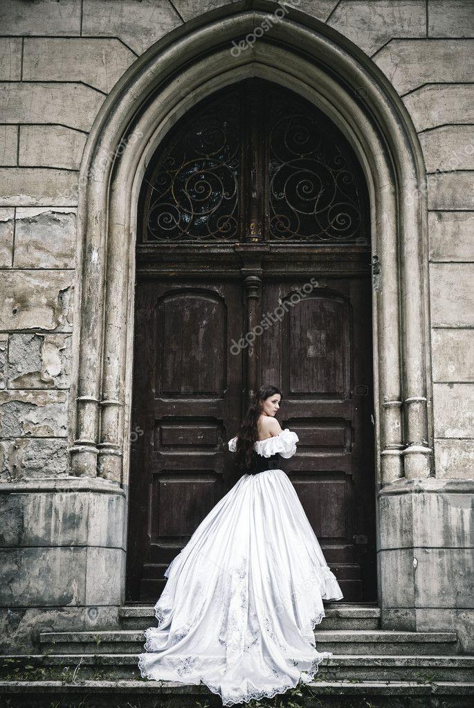 misteriosa mujer en vestido victoriano con puertas antiguas u foto de stock