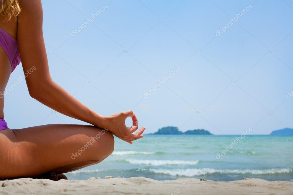 Woman in lotus position meditating on the beach