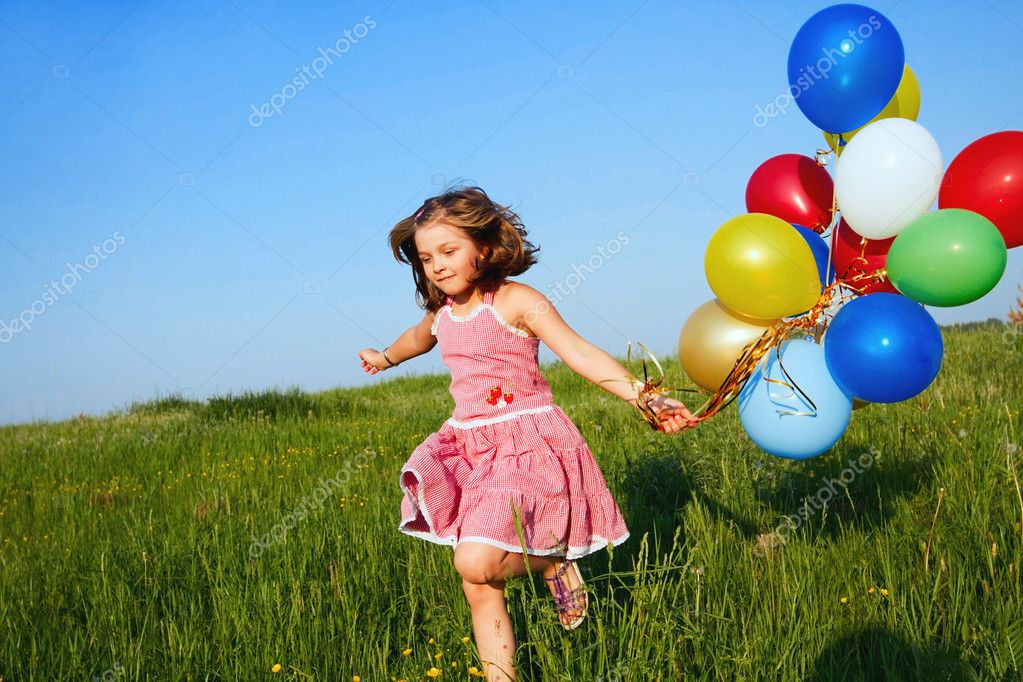 Happy little girl jumping outdoors with balloons