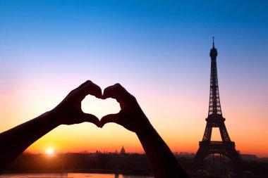Hands making heart against Eiffel Tower