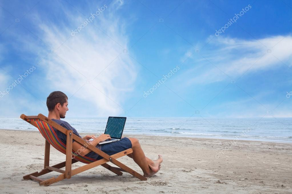 Working with computer on the beach