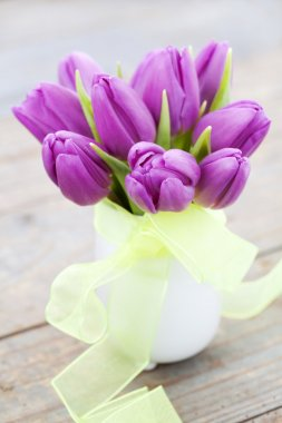 Bouquet of purple tulips and mimosa in vase on wooden background stock vector