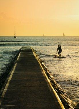 Waikiki pier and paddleboarding man