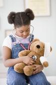 Fotografie africká americká dívka drží stetoskop na medvídka